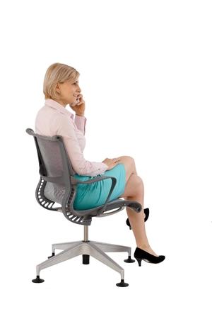 Zakenvrouw zitten in bureaustoel, praten over de mobiele telefoon. Witte achtergrond, full size.
