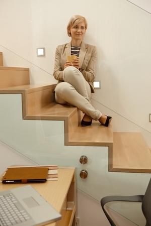 Daydreaming blonde woman sitting in stairway, looking away.
