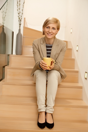 Happy young woman sitting in stairway, smiling, looking at camera. Full size.