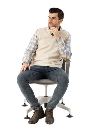 hombre sentado: Hombre de negocios joven sentado en la silla giratoria sobre fondo blanco, pensando, mirando de lejos. Mano en la barbilla.