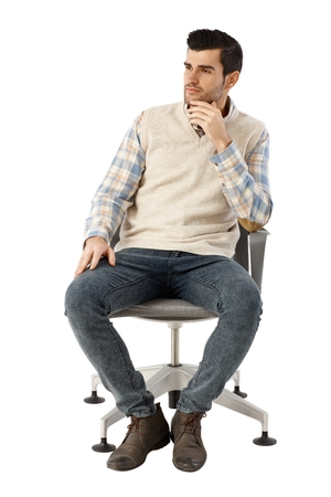 sit: Young businessman sitting in swivel chair over white background, thinking, looking away. Hand on chin.