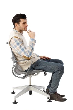Vista lateral del hombre de negocios pensando en la silla giratoria sobre fondo blanco. Foto de archivo