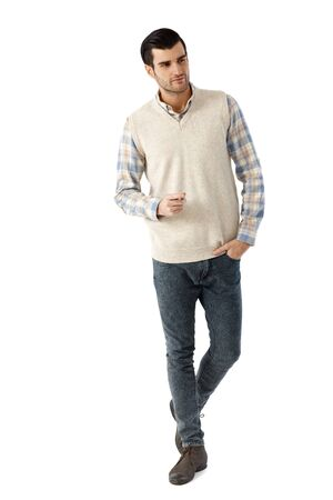 full size: Young man walking over white background with hand in pocket, looking away. Stock Photo