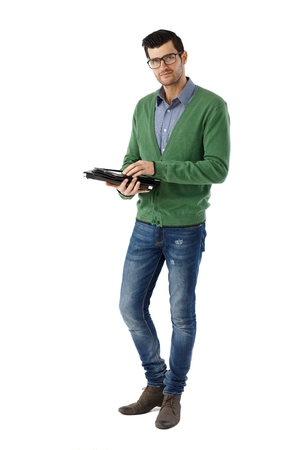 Casual young man standing over white background using tablet Фото со стока