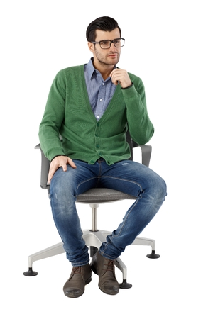 full size: Young businessman sitting in swivel chair over white background, thinking. Full-length.