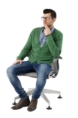 image size: Young businessman sitting in swivel chair over white background, looking away, thinking. Full size.