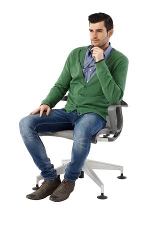 Beau jeune homme d'affaires assis et penser en chaise pivotante sur fond blanc, regarder, loin. Taille réelle.