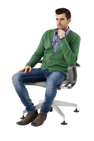 swivel chairs: Handsome young businessman sitting and thinking in swivel chair over white background, looking away. Full size.