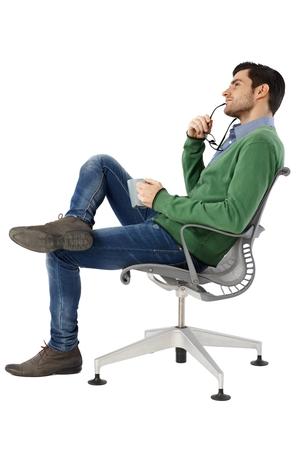 回転椅子に座っている若い男が空想の側面図