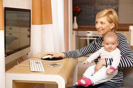 madre trabajando: Madre joven que trabaja en el ordenador mientras mantiene la niña en el regazo, sonriendo. Foto de archivo