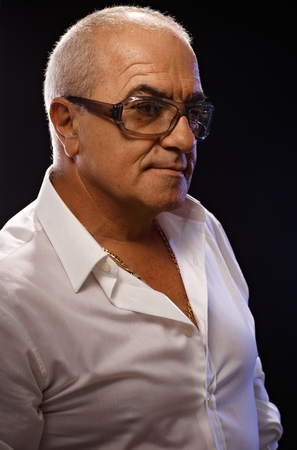 55 to 60: Portrait of casual old man in white shirt and glasses over black background. Side view. Stock Photo
