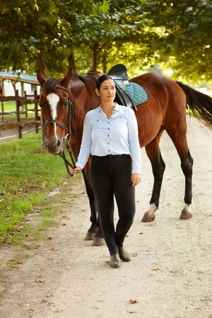 Female rider walking with horse in the green, daydreaming. photo