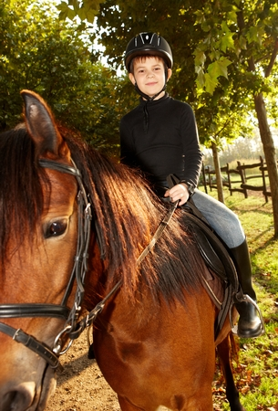 Cute little boy sitting on horseback in nature, smiling. Stock Photo