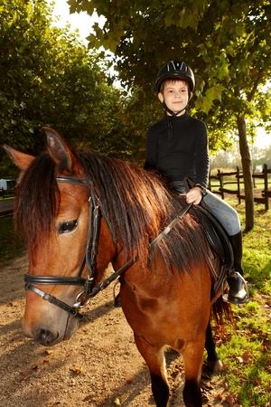 parapente: Niño pequeño lindo paseos a caballo en el verde en otoño. Foto de archivo