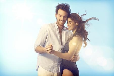 pareja bailando: Romántico joven pareja de baile de amor al aire libre bajo el cielo azul en verano. Foto de archivo