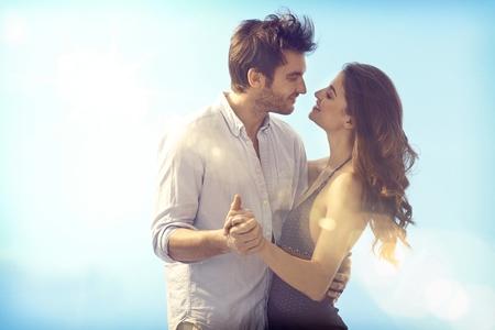 Pares loving felizes se abraçando e beijando ao ar livre no verão sob o céu azul.