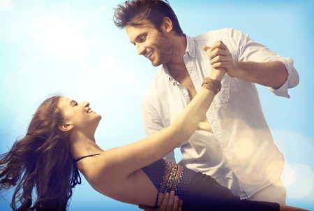 Feliz pareja romántica bailando al aire libre bajo el cielo azul.