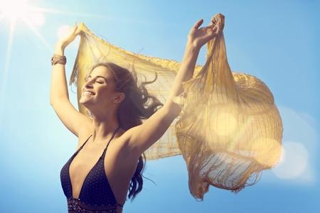 woman bathing: Beautiful young woman enjoying sunshine and light wind at summertime eyes closed, lifting shawl high up. Stock Photo