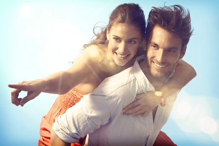 Romantic loving couple piggyback on summer holiday.