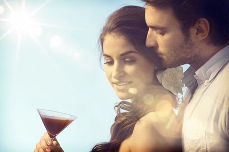 be kissed: Romantic couple on summer holiday enjoying sunset with a drink.