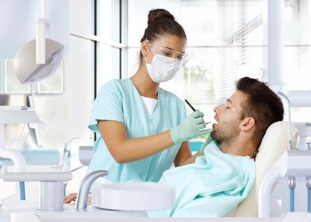 Jonge man op tandheelkundige check-up, door vrouwelijke tandarts onderzocht. Stockfoto