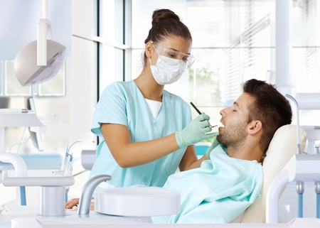 dental care: Young man on dental check-up, examined by female dentist.