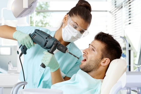 dentist drill: Aggressive female dentist drilling tooth with power drill.
