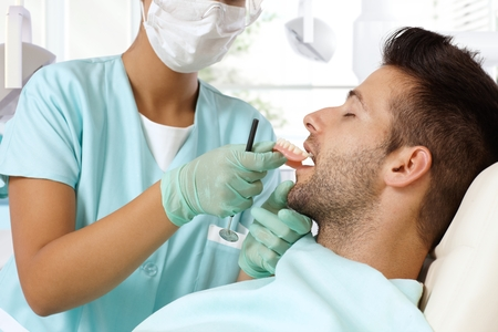 Dentist trying in denture to young patients mouth. photo