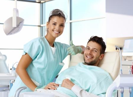 Portret van aantrekkelijke vrouwelijke tandarts blijkt duim-omhoog teken, terwijl de patiënt lachend in de stoel van de tandarts.