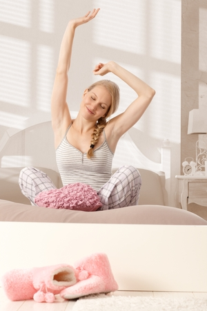 tailor seat: Young blonde woman sitting in tailor seat, stretching in bed in the morning, smiling eyes closed.