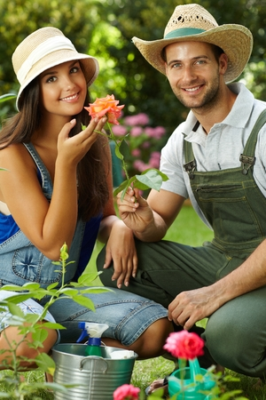 Happy gardening couple smiling at camera, smelling rose, smiling. photo