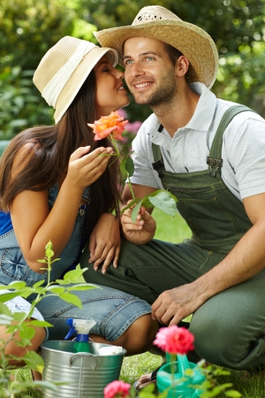 be kissed: Happy gardening couple kissing, holding rose, smiling.
