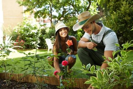 en cuclillas: Pareja joven jardinería exterior, sonriendo feliz.