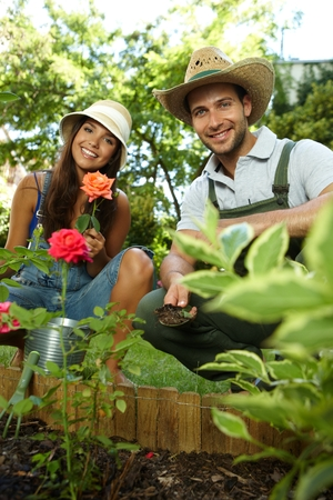 Young romantic couple gardening at springtime, smiling happy. photo