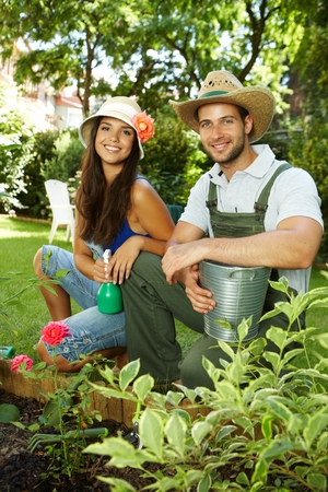 Attractive young couple gardening, smiling happy. photo