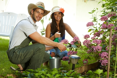 to crouch: Attractive young couple gardening together at springtime, smiling happy. Stock Photo