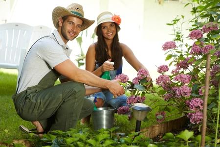 en cuclillas: Pareja joven y atractiva jardinería juntos en primavera, sonriendo feliz.