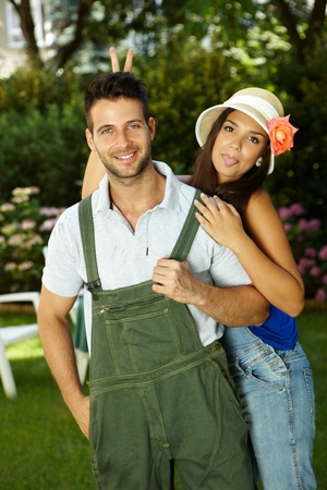 Young couple having fun in the garden, woman sticking tongue, smiling happy. photo