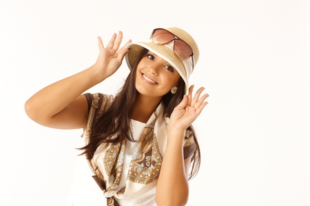 regulating: Summer portrait of attractive young woman regulating hat, smiling happy. Stock Photo