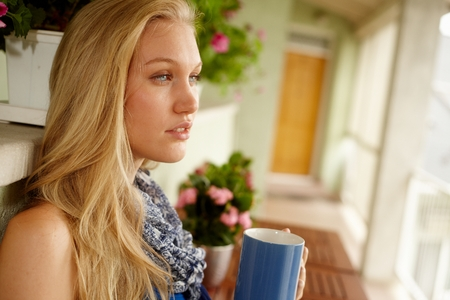 Side view of young blonde female drinking tea in balcony. Stock Photo