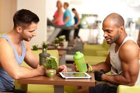 tomando refresco: Hombres j�venes atl�ticos sentado a la mesa en el gimnasio, en un descanso, beber refresco, con tablet PC.