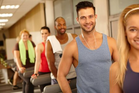 earbuds: Handsome man smiling in gym with earbuds, training among others.