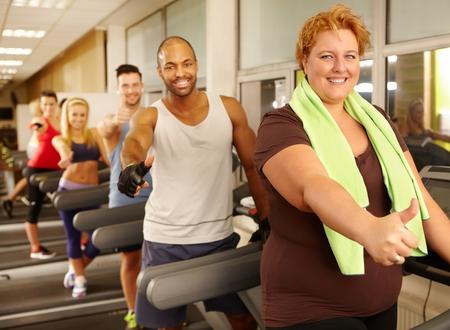 sobre peso: Entrenamiento de la mujer gorda con los demás en el gimnasio, todos los que muestran los pulgares para arriba.