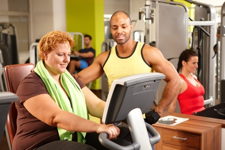 Fat woman doing workout on exercise bike with supervision of personal trainer. photo