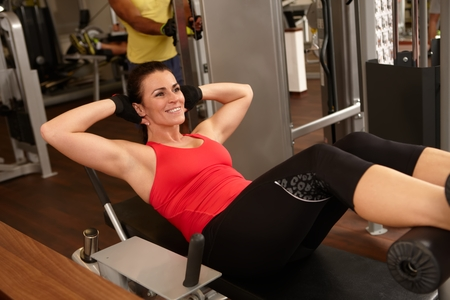 Fit woman doing sit-ups in gym, smiling. photo