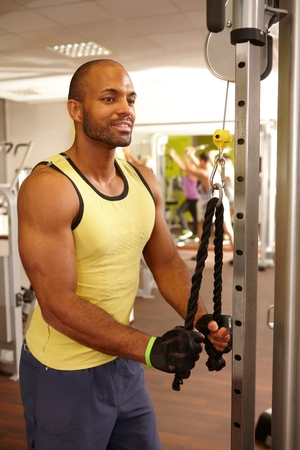weight machine: Athletic black man training on weight machine in gym.