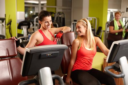 fit women: Two fit women talking in gym, exercising.