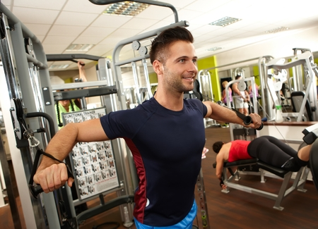 weight machine: Handsome sporty young man training on weight machine in gym.