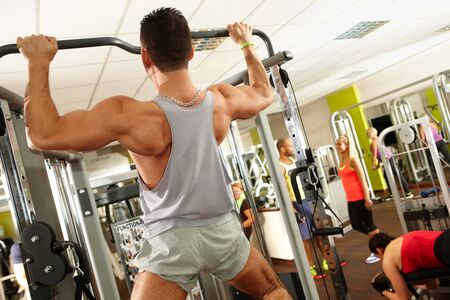 vital: Muscular man training in gym, doing pull-up workout.