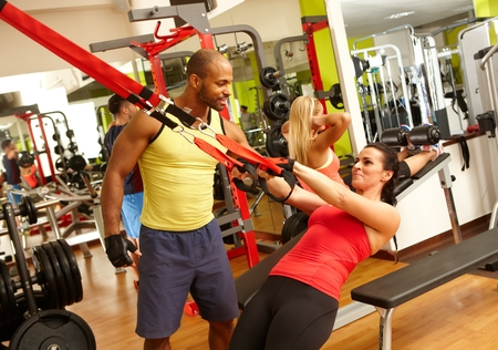 Fit woman doing TRX suspension training workout in gym with the guidance of personal trainer. photo